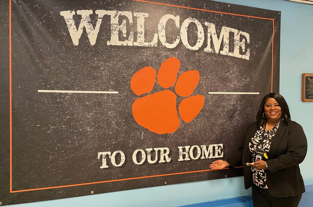 new principal in front of Welcome to our Home banner