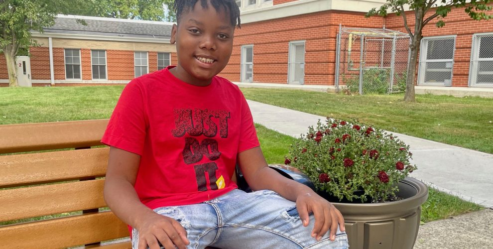 fifth-graders smiling on bench outside school