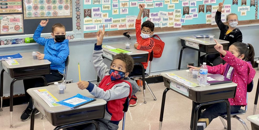 second-graders raising their hands